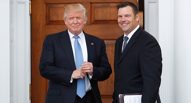 President-elect Donald Trump pauses to pose for photographs as he greets Kansas Secretary of State, Kris Kobach, at the Trump National Golf Club Bedminster clubhouse, Sunday, Nov. 20, 2016, in Bedminster, N.J.. (AP Photo/Carolyn Kaster)