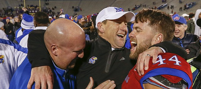 Kansas head coach David Beaty is flanked by fullback Michael Zunica (44) and offensive line coach Zach Yenser following the Jayhawks' 24-21 overtime upset of Texas on Saturday, Nov. 19, 2016 at Memorial Stadium.