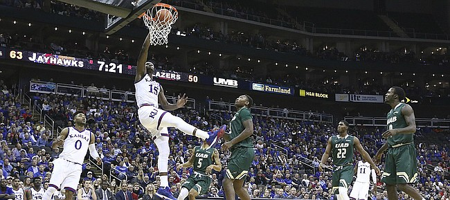 Kansas forward Carlton Bragg Jr. (15) finishes a dunk off a lob from teammate Devonte' Graham during the second half of the CBE Classic on Monday, Nov. 21, 2016 at Sprint Center.