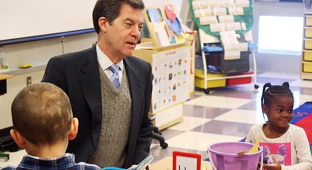 Kansas Gov. Sam Brownback listens to kindergarten students discuss Jayhawks during class Thursday, Jan. 23, 2014, at Roesland Elementary School in Roeland Park, Kansas. (AP Photo/John Milburn)