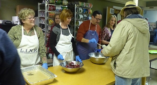 Frank Ybarra serves a man during the annual LINK Thanksgiving dinner on Nov. 24, 2016. Mary Olson, Janet Buie, Ybarra and Samantha Hauber were among about 150 volunteers who helped prepare, serve and deliver Thanksgiving meals for about 800 people.