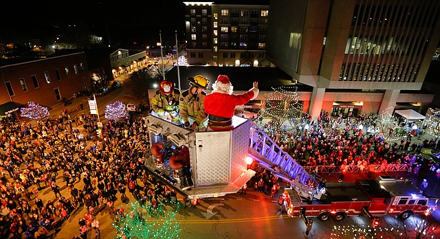 Hundreds of children, parents and Lawrence residents gather below at the intersection of Ninth and Massachusetts streets as Santa Claus is heroically rescued from the roof of Weaver's department store by two Lawrence firefighters in a ladder truck Friday evening, Dec. 4, 2015.
