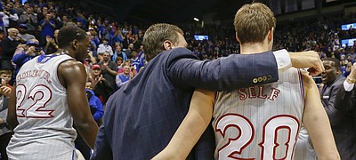 Kansas head coach Bill Self gets a hug from his son Tyler Self as he leaves the floor with his 600th win.