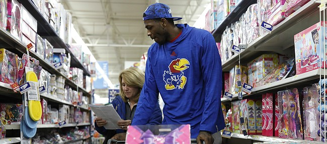 Cindy Self, wife of Kansas men's basketball coach Bill Self, shops for toys with KU junior Dwight Coleby as he and other members of the Kansas men's basketball team shopped at the Iowa Street Wal-Mart on Thursday night, purchasing Christmas gifts for Lawrence families in conjunction with the Salvation Army.