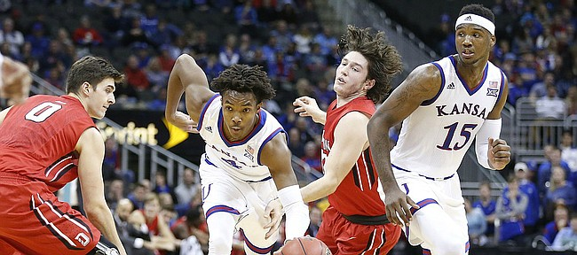 Kansas guard Devonte' Graham (4) finds a hole as he cuts between Davidson forward Dusan Kovacevic (0) and Davidson guard Rusty Reigel (32) during the second half, Saturday, Dec. 17, 2016 at Sprint Center. At right is Kansas forward Carlton Bragg Jr. (15).