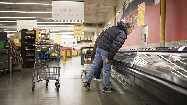 Lawrence resident Lance Fahy, who is visually impaired, leans in closely to see the labels on packages of ground beef while doing his shopping on Thursday, Dec. 15, 2016.