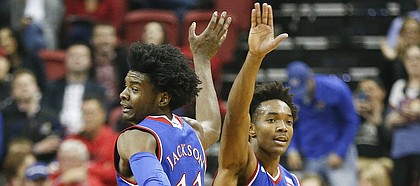 Kansas guard Josh Jackson (11) gets a high five from Kansas guard Devonte' Graham (4) after a dunk during the first half, Thursday, Dec. 22, 2016 at Thomas & Mack Center in Las Vegas.