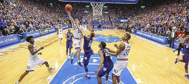 With a hand in his face, Kansas guard Sviatoslav Mykhailiuk (10) puts in the final bucket to give the Jayhawks a 90-88 win over Kansas State on Tuesday, Jan. 3, 2017 at Allen Fieldhouse.