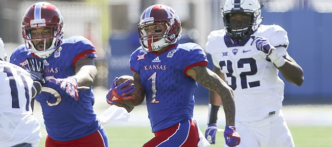 Kansas wide receiver LaQuvionte Gonzalez (1) gets a block from teammate Bobby Hartzog Jr. (5) as he runs for a 70-yard gain during the third quarter on Saturday, Oct. 8, 2016 at Memorial Stadium.