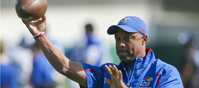 Kansas wide receivers coach Jason Phillips throws passes to his players during practice on Tuesday, April 5, 2016.