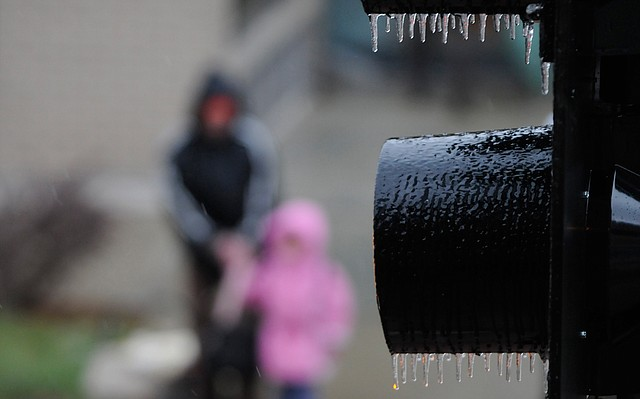In this file photo from March 28, 2009, a mother and child wait for the crosswalk sign outside the Lawrence Art Center as freezing rain falls and icicles form on the stoplights.