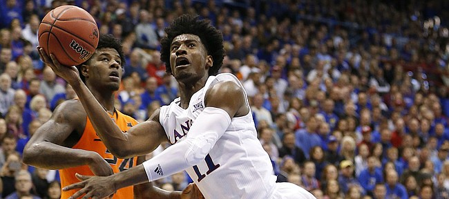 Kansas guard Josh Jackson (11) tosses up a shot after losing his footing during the second half, Saturday, Jan. 14, 2017 at Allen Fieldhouse. At left is Oklahoma State guard Davon Dillard (24).
