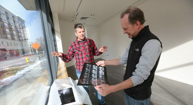 Photographer Mike Yoder looks through prints of contact sheets with Lawrence Arts Center exhibition program director Ben Ahlvers on Monday, Jan. 9, 2017 in the front gallery at the Lawrence Arts Center.