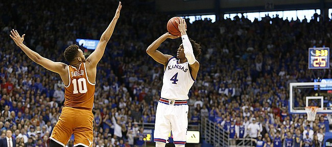 Kansas guard Devonte' Graham (4) lines up a three over Texas guard Eric Davis Jr. (10) during the first half, Saturday, Jan. 21, 2017 at Allen Fieldhouse.