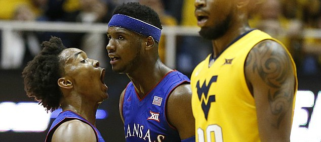 Kansas guard Devonte' Graham (4) tries to pump up teammate Carlton Bragg (15) in front of West Virginia forward Lamont West (15) during the first half, Tuesday, Jan. 24, 2017 at WVU Coliseum.