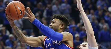 Kansas guard Frank Mason III (0) gets past Kentucky forward Isaac Humphries (15) for a bucket during the first half, Saturday, Jan. 28, 2017 at Rupp Arena in Lexington, Kentucky.