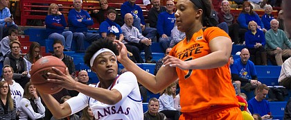 Kansas' Aisia Robertson (15) goes up for the layup over Oklahoma State's Diana Omozee (5) Wednesday at Allen Fieldhouse.