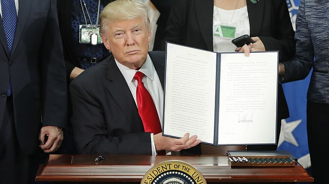 President Donald Trump holds up an executive order for border security and immigration enforcement changes after signing the order during a visit to the Homeland Security Department headquarters in Washington, D.C., Wednesday, Jan. 25, 2017.