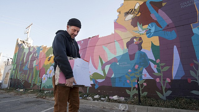 "In this file photo from March 6, 2015, Lawrence artist Dave Loewenstein holds a piece of his ""Pollinators"" mural after construction workers began to dismantle the artwork at Ninth and New Hampshire streets."