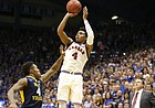 Kansas guard Devonte' Graham (4) hits a three over West Virginia guard Daxter Miles Jr. (4) in overtime, Monday, Feb. 13, 2017 at Allen Fieldhouse.
