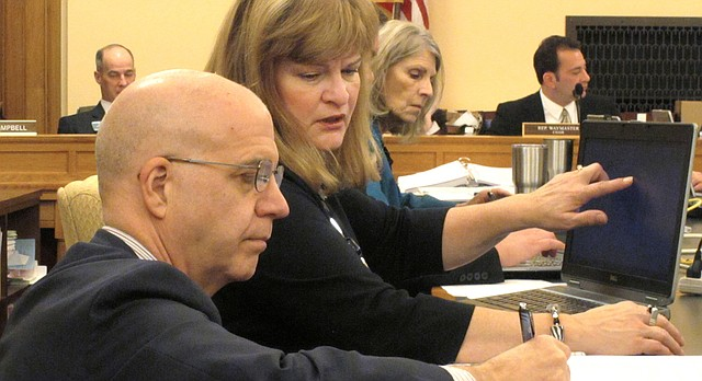 J.G. Scott, left, the chief fiscal analyst for the Kansas Legislative Research Department, confers with Bobbi Mariani, another fiscal analyst, during a meeting of the Kansas House Appropriations Committee, Monday, Feb. 13, 2017, at the Statehouse in Topeka, Kan. The committee has endorsed budget-balancing proposals that would allow the state to avoid cuts in education funding. (AP Photo/John Hanna)