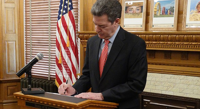 Gov. Sam Brownback vetoes a $1 billion income tax bill that would reverse many of the tax policies he championed in 2012.