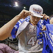 Kansas forward Mitch Lightfoot (44) and Kansas guard Devonte' Graham (4) celebrate with a 13-straight conference title towel following the Jayhawks' win over TCU.