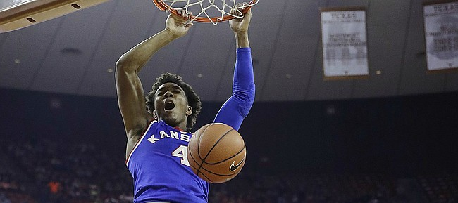 Kansas guard Devonte' Graham (4) scores over Texas guard Eric Davis Jr. (10) during the first half of an NCAA college basketball game, Saturday, Feb. 25, 2017, in Austin, Texas.