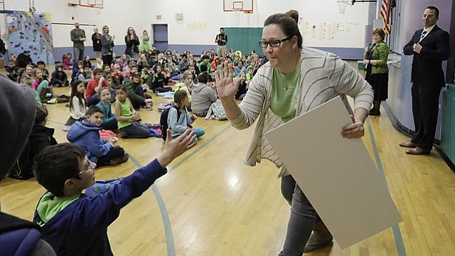 Woodlawn Elementary School fifth-grader Anthony Poe, seated left, high-fives school secretary Andrea Anderson after Anderson was honored with the Lawrence school district's Class Act Award in a school assembly on Thursday, March 2, 2017.
