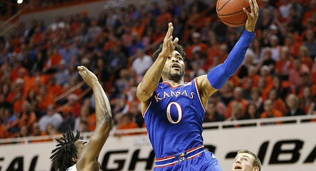Kansas guard Frank Mason III (0) gets in for a bucket between Oklahoma State guard Brandon Averette (0) and Oklahoma State guard Phil Forte III (13) during the first half, Saturday, March 4, 2017 at Gallagher-Iba Arena.