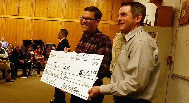 Jack Hood, left, Lawrence Public Schools' 2017 Secondary Teacher of the Year, poses with his $1,000 check and Tim Mock, right, Truity Credit Union's business development officer, during the Teacher of the Year ceremony Wednesday at Lawrence High School. Superintendent Kyle Hayden surprised Hood, a history and economics teacher at LHS, with the district's annual award that morning.