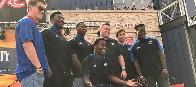 Kansas football players Carter Stanley, Daniel Wise, Dorance Armstrong Jr., Joe Dineen, Peyton Bender, Daylon Charlot and Mike Lee (center) pose for photos at the Power & Light District in Kansas City, Mo., on March 9, 2017.