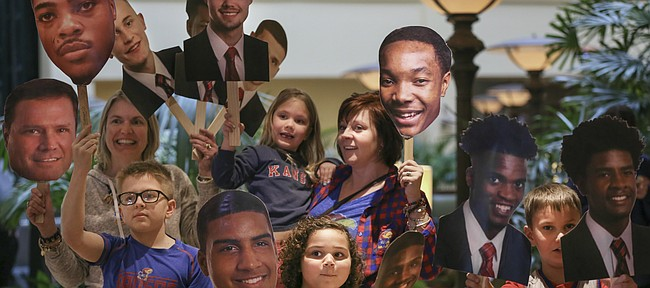 Kansas basketball fans, clockwise from center, Annika Rowcroft, 7, Anderson Rowcroft, 10, Beth Menghini, Katie Menghini, 5, Rhonda Beffort and Anthony Menghini, 8, right, wave photographs of the Jayhawks as they wait for head coach Bill Self to finish interviews with media members upon the team's arrival Wednesday, March 15, 2017 at the Renaissance Hotel in Tulsa, Okla.