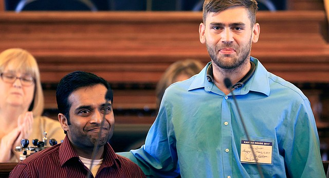 Alok Madasani, left, and Ian Grillot, right, embrace and smile after they were honored by the Kansas House of Representatives in Topeka, Kan., Thursday, March 16, 2017. House Speaker Ron Ryckman, Jr. recognized the two survivors of last month's shooting at an Olathe bar and commemorated Srinivas Kuchibhotla, who died in the shooting. House members also passed a resolution honoring Kuchibhotla's life. (AP Photo/Orlin Wagner)