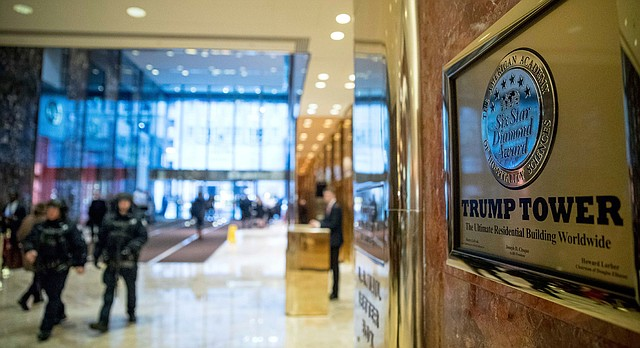 In this Tuesday, Jan. 17, 2017, file photo, police officers walk through the lobby of Trump Tower in New York. (AP Photo/Andrew Harnik, File)