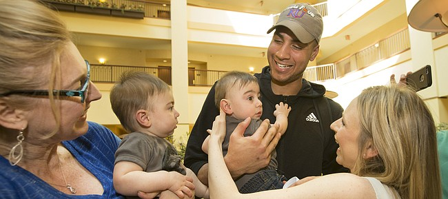 Kansas forward Landen Lucas smiles as he is handed ten-month-old Lucas Sadler along with his twin brother Landon Sadler, left, during a meeting with their parents Meredith Sadler, right, and her husband Ian Sadler, not pictured, of Tulsa on Saturday, March 18, 2017 at the Renaissance Hotel in Tulsa, Okla. Also present for the meeting was Landen Lucas' mother, Shelley Lucas, who bought basketballs for the twins who were named after her son.
