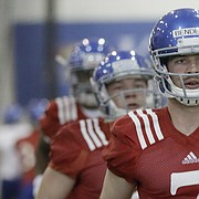 Kansas junior quarterback Peyton Bender (No. 7) runs through warm-ups with teammates at the start of a recent spring football practice.