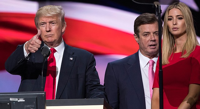 In this photo taken July 21, 2016, then-Trump Campaign manager Paul Manafort stands between the then-Republican presidential candidate Donald Trump and his daughter Ivanka Trump during a walk through at the Republican National Convention in Cleveland. (AP Photo/Evan Vucci)