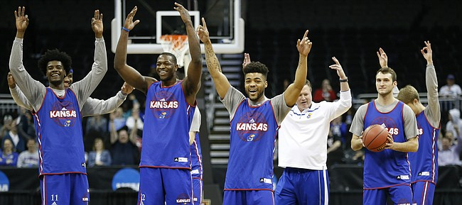 The Jayhawks celebrate a half-court shot by teammate Devonte' Graham during a day of practices and press conferences prior to Thursday's game at Sprint Center in Kansas City, Mo.