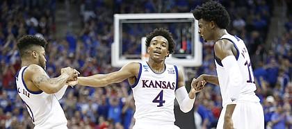 Kansas guard Frank Mason III (0) and Kansas guard Josh Jackson (11) help up Kansas guard Devonte' Graham (4) after Graham hit a three during the second half, Thursday, March 23, 2017 at Sprint Center in Kansas City, Mo.