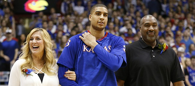 Kansas forward Landen Lucas (33) walks out on Senior Night with his mother, Shelley, and father, Richard.
