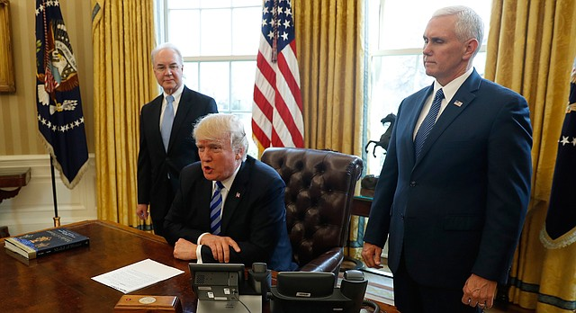 President Donald Trump, flanked by Health and Human Services Secretary Tom Price, left, and Vice President Mike Pence, meets with members of the media regarding the health care overhaul bill, Friday, March 24, 2017, in the Oval Office of the White House in Washington. (AP Photo/Pablo Martinez Monsivais)