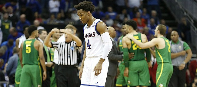 A deflated Kansas guard Devonte' Graham walks to the bench during a KU timeout in the second half on Saturday, March 25, 2017 at Sprint Center.