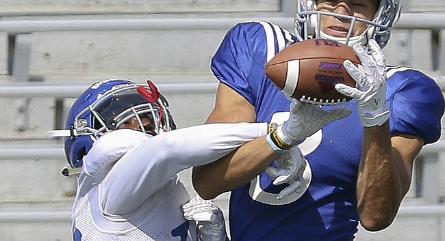 FILE — Kansas receiver Chase Harrell, right, tries to hold on to a pass as defensive back Kyle Mayberry pulls down on his arm during KU's Fan Appreciation Day practice on Saturday, August 20, 2016, at Memorial Stadium.