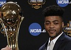Associated Press Deputy Director of Sports Products Barry Bedlan hands Kansas' Frank Mason III stands answers his AP Player of the Year trophy at a news conference Thursday, March 30, 2017, in Glendale, Ariz. (AP Photo/Matt York)