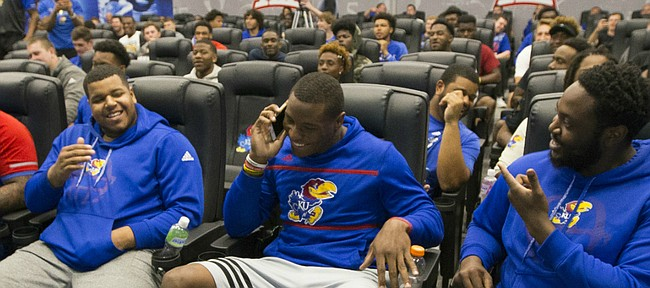 Kansas defensive end Dorance Armstrong Jr., front and center, gets a call from co-defensive coordinator and cornerbacks coach Kenny Perry notifying him that Perry had selected Armstrong as the second overall pick during a spring game player draft on Wednesday, April 12, 2017 at the Anderson Family Football Complex.