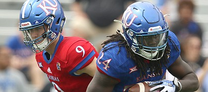 Team KU running back Taylor Martin (24) takes a handoff from Team KU quarterback Carter Stanley (9) during the first quarter of the 2017 Spring Game on Saturday, April 15 at Memorial Stadium.