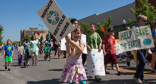 A young girl holds up a sign encouraging people to recycle as she walks with other parade marchers down Massachusetts Street at the Earth Day Parade and Celebration in South Park on Saturday, April 23, 2016.