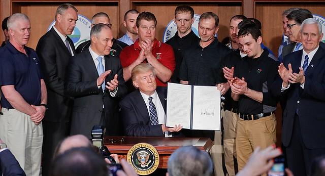 President Donald Trump, accompanied by Environmental Protection Agency (EPA) Administrator Scott Pruitt, third from left, and Vice President Mike Pence, right, is applauded as he hold up the signed Energy Independence Executive Order, Tuesday, March 28, 2017, at EPA headquarters in Washington. (AP Photo/Pablo Martinez Monsivais)
