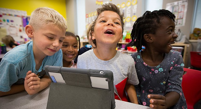 Sunset Hill kindergartners Coby Robben, left, Mila Sims, Manny Ellis and Ambra Atakere, right, react to a video clip sent to them by a kindergartner in Shanghai, China, while crowded around an iPad on Tuesday, April 25, 2017 at the school. Through a pen-pal correspondence with the Chinese students, teacher Nicole Corn's kindergartners have been learning about the many cultural similarities and differences through posts about their lives at school and home, their favorite foods and also favorite activities.